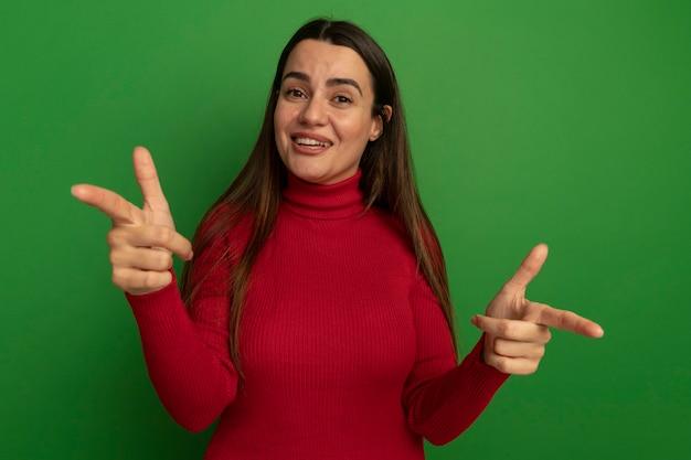 녹색 벽에 고립 된 두 손으로 앞에 웃는 예쁜 여자 포인트