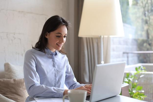 Улыбается красивая женщина, сидящая за столом, глядя на экран ноутбука. счастливый предприниматель читает электронное письмо с хорошими новостями, болтает с клиентами в интернете.
