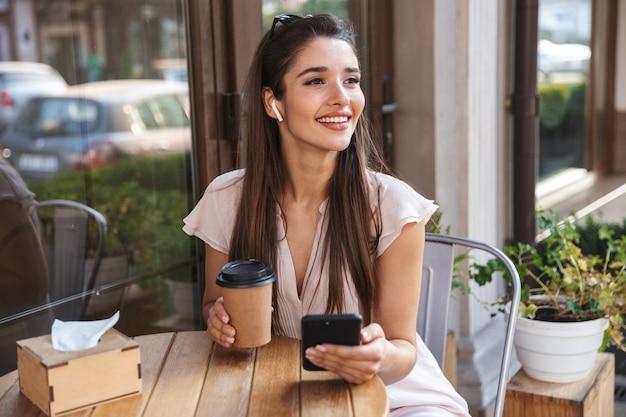 屋外のカフェに座って、コーヒーを飲み、携帯電話を使用してきれいな女性の笑顔