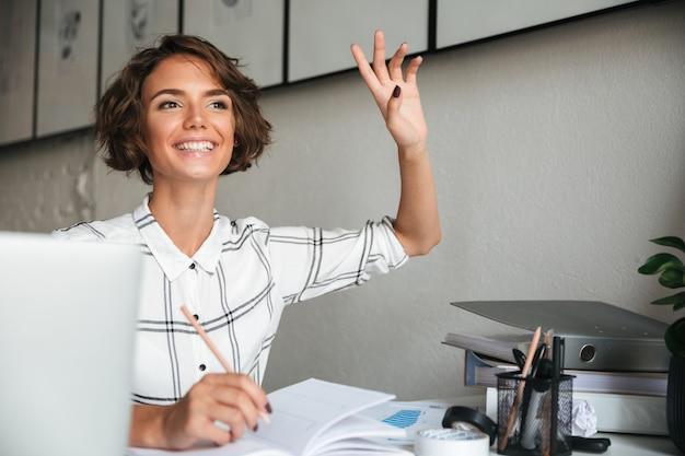 Donna graziosa sorridente che si siede dalla tabella
