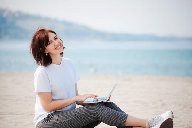 彼女のラップトップとビーチに座っているきれいな女性の笑顔