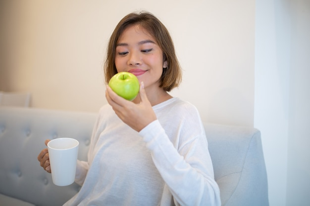 Smiling pretty woman sitting on sofa with apple and tea mug