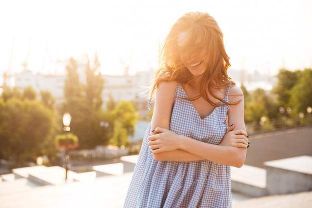 Улыбка красивая женщина, стоя с сложив и смеясь