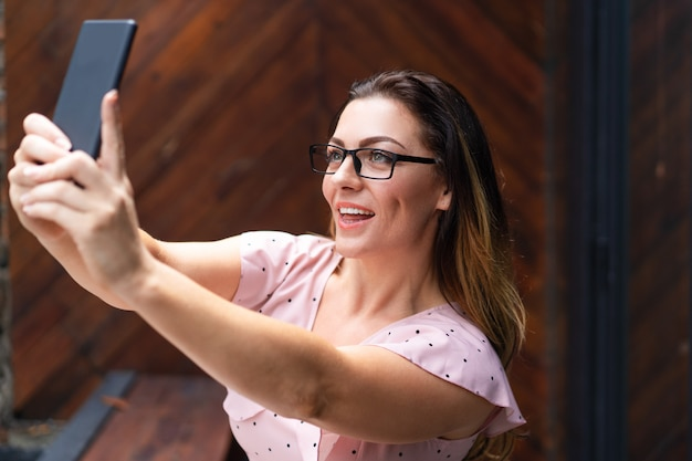Smiling pretty woman taking selfie photo on smartphone in cafe
