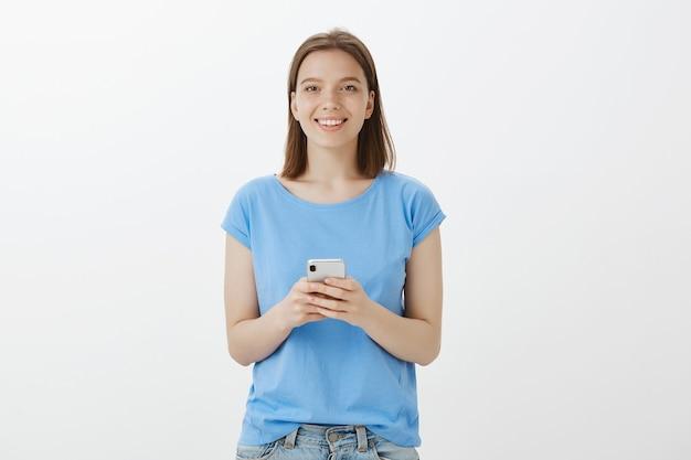 Donna graziosa sorridente che utilizza smartphone, messaggio di testo o applicazione di download