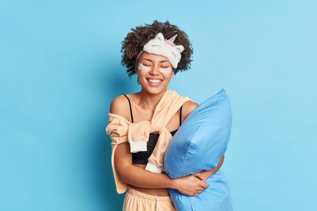 Sorridente bella donna con i capelli afro non vuole svegliarsi come vede un piacevole sogno dolce sta con gli occhi chiusi vestito in indumenti da notte tiene il cuscino si rilassa a casa