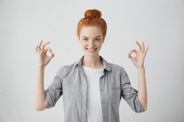 Улыбающаяся симпатичная женщина с рыжими волосами в рубашке, показывающая знак ок, с пальцами, имеющими откровенную улыбку, наслаждаясь своей жизнью, надеясь, что все будет отлично. люди и счастье