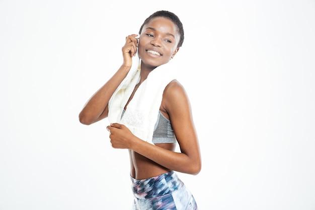Улыбается довольно молодая афро-американская спортсменка с полотенцем на шее
