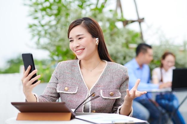 彼女の同僚や友人にビデオ通話するときにスマートフォンを使用してかなり若いアジアのビジネス女性を笑顔