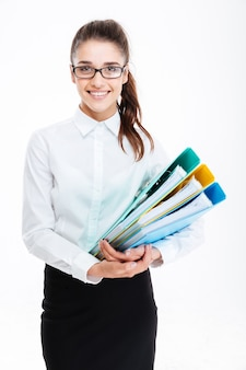 Smiling pretty young business woman in glasses holding folders with documents over white wall