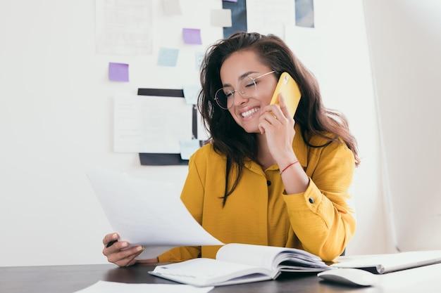 Улыбается довольно молодая бизнесвумен в очках, сидя на рабочем месте девушка в желтой рубашке читает газету и обсуждает на своем телефоне это с клиентом