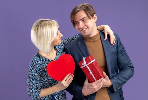 Улыбаясь симпатичная молодая пара, глядя друг на друга, держа в руках подарочную коробку и красное сердце в день святого валентина
