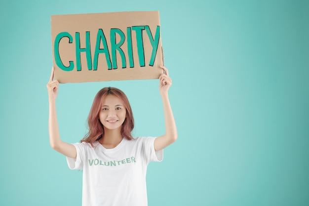 Улыбающаяся симпатичная молодая женщина-волонтер держит благотворительный бумажный знак над головой