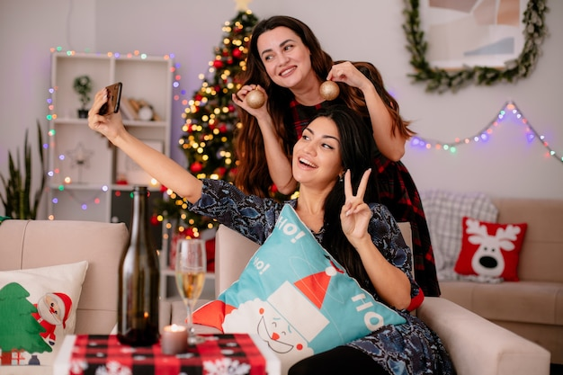肘掛け椅子に座って笑顔のかわいい若い女の子が勝利のサインをジェスチャーし、自宅でクリスマスの時間を楽しんでいるガラス玉の飾りを持っている彼女の友人と一緒に自分撮りをします