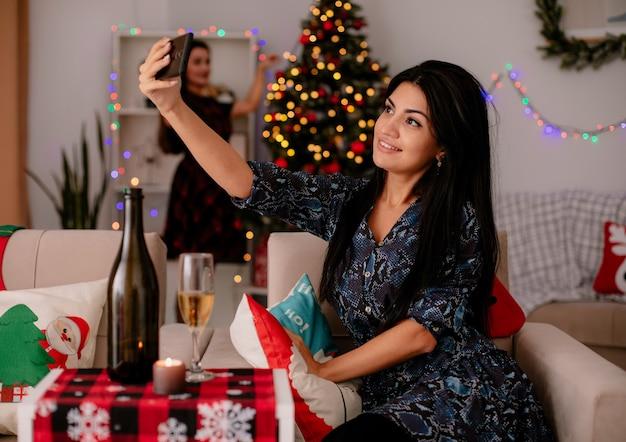 笑顔のかわいい若い女の子が肘掛け椅子に座って自分撮りを取り、彼女の友人は家でクリスマスの時間を楽しんで後ろにクリスマスツリーを飾る
