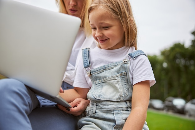 도시 공원에서 노트북에서 엄마와 함께 시간을 보내는 동안 데님 장난 꾸러기를 입고 웃는 예쁜 어린 소녀