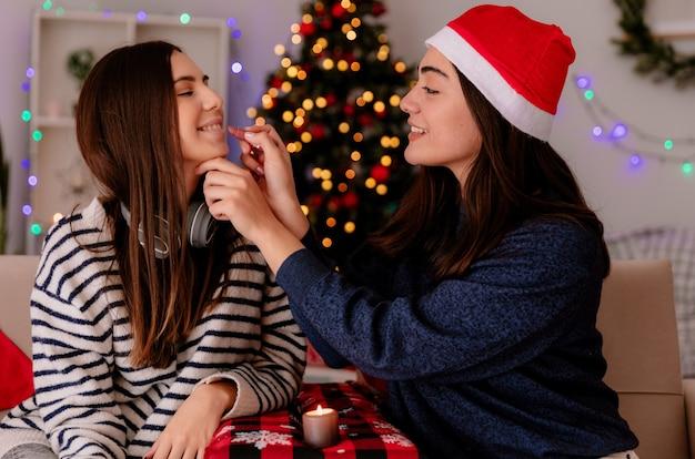 Una bella ragazza sorridente con un cappello da babbo natale trucca i suoi amici seduti sulla poltrona e si gode il periodo natalizio a casa