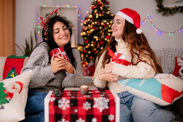 산타 모자와 함께 웃는 예쁜 어린 소녀는 선물 상자를 보유하고 홀리 화환이 안락 의자에 앉아 집에서 크리스마스 시간을 즐기는 그녀의 만족스러운 친구를 봅니다.