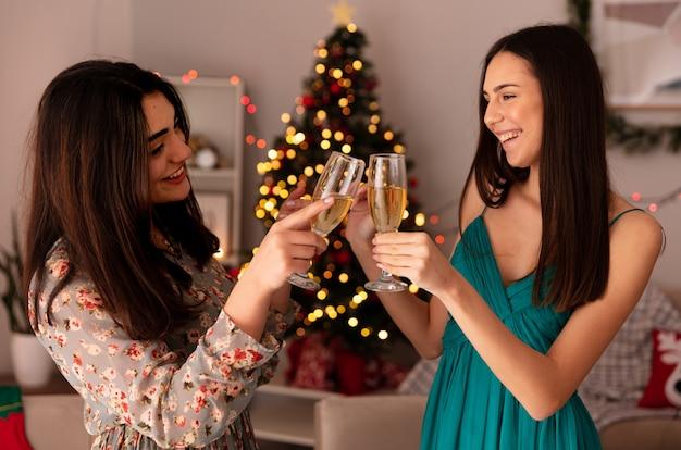 Sorridenti belle ragazze tintinnano bicchieri di champagne godendo il periodo natalizio a casa