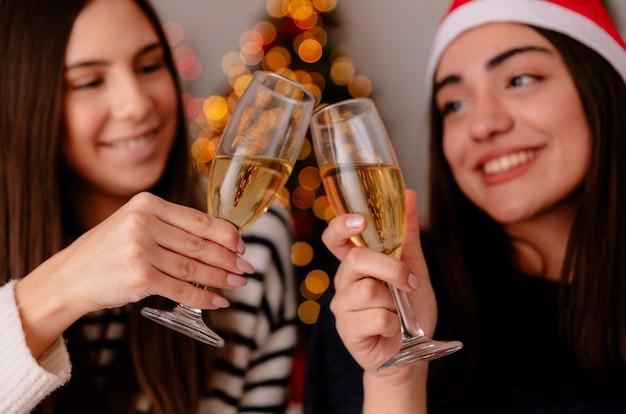 Sorridenti ragazze graziose brindano bicchieri di champagne seduti sulle poltrone il tempo di natale a casa