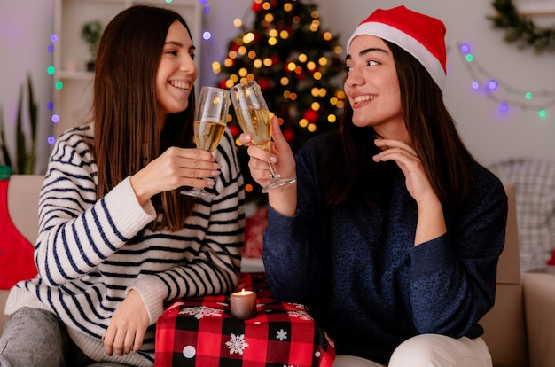 笑顔のかわいい若い女の子がシャンパンのグラスをチャリンという音を立てて、アームチェアに座ってお互いを見て、家でクリスマスの時間を楽しんでいます