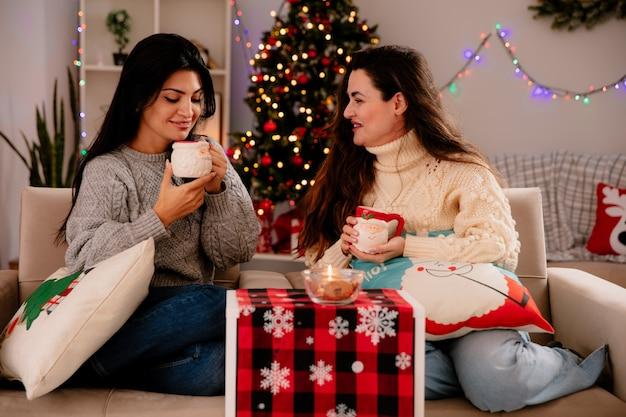 Ragazze carine sorridenti tengono e guardano le tazze seduti sulle poltrone e si godono il periodo natalizio a casa