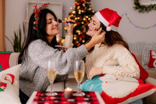 Улыбающиеся симпатичные молодые девушки держат кисти для пудры, делают друг другу макияж, сидя на креслах и наслаждаясь рождеством дома