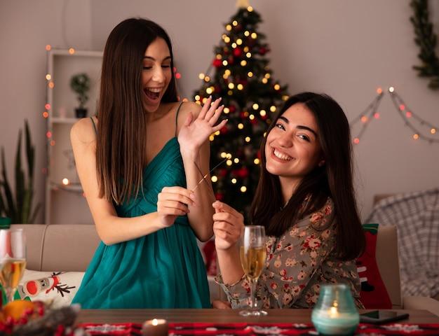 웃는 예쁜 어린 소녀는 폭죽을 잡고 테이블에 앉아 집에서 크리스마스 시간을 즐기는 카메라를 봅니다.