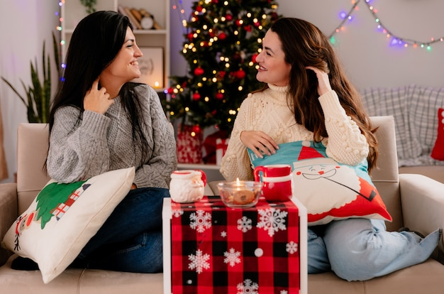 웃는 예쁜 젊은 여자가 서로 안락 의자에 앉아 머리를 들어 올려 집에서 크리스마스 시간을 즐기는 모습