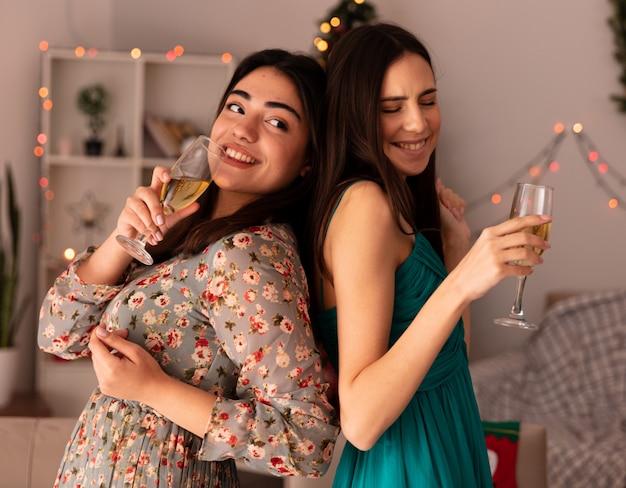 Sorridenti belle ragazze stanno schiena contro schiena tenendo bicchieri di champagne godendo il periodo natalizio a casa