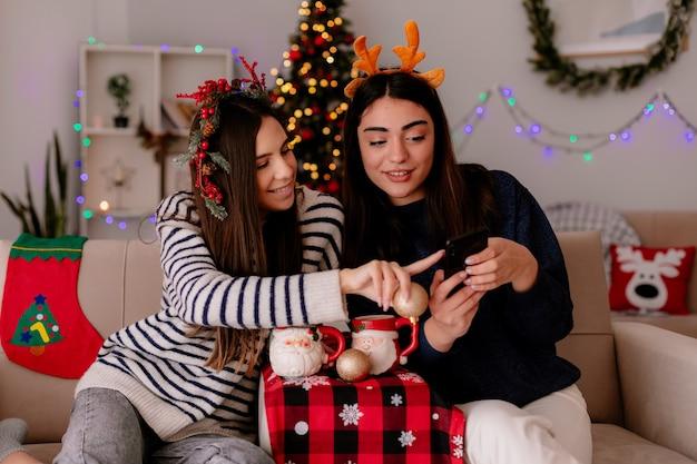 Улыбающиеся симпатичные молодые девушки с венком из падуба и ободком с оленями смотрят на телефон, сидя на креслах и наслаждаясь рождеством дома
