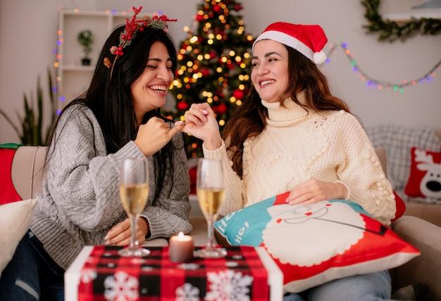 Sorridenti ragazze graziose con il cappello di babbo natale incrociano le dita sedute sulle poltrone e si godono il periodo natalizio a casa