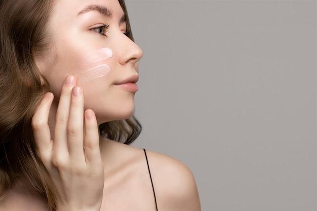 保湿クリーム、指で顔にローション、灰色の背景、コピースペースを適用して笑顔のかなり若い女性。健康的な治療と美容製品。美容ルーチン、スキンケアの概念