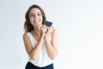 Smiling pretty young woman holding plastic card