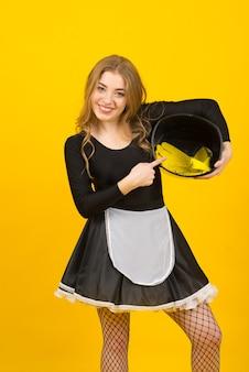 Улыбаясь домохозяйка довольно молодая женщина в повседневной одежде, делая работу по дому, изолированные на желтом фоне студийный портрет. концепция домашнего хозяйства. копируйте пространство для копирования.