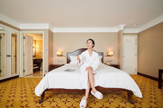部屋のベッドに座って、朝のコーヒーを飲むバスローブでかなり若い女性の笑顔