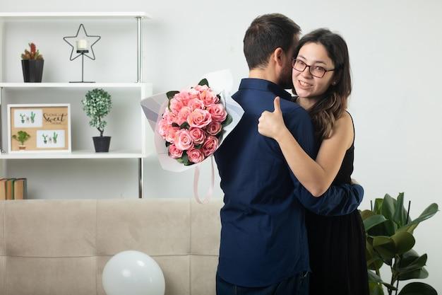 안경을 쓴 예쁜 젊은 여성이 꽃다발을 들고 거실에 서 있는 잘생긴 남자를 껴안고 엄지손가락을 치켜듭니다.