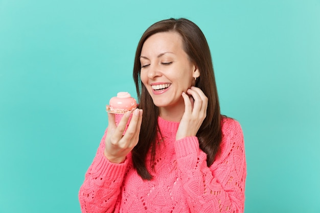 Smiling pretty young woman in knitted pink sweater holding in hand cake isolated on blue turquoise wall background, studio portrait. people sincere emotions, lifestyle concept. mock up copy space.