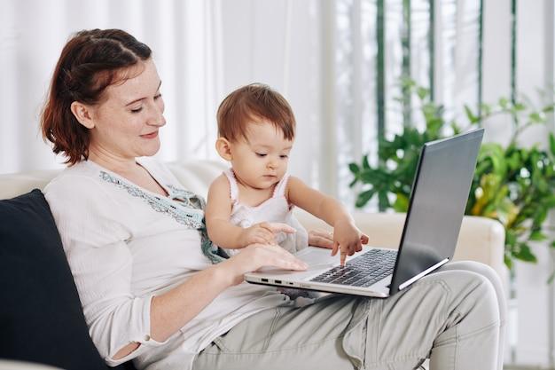 Улыбается довольно молодая женщина, позволяя дочери нажимать кнопки на ноутбуке