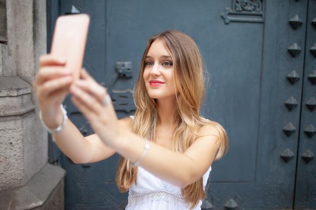 Giovane donna graziosa sorridente che si fotografa