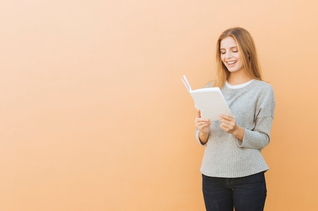 Smiling pretty young woman reading book against colored background