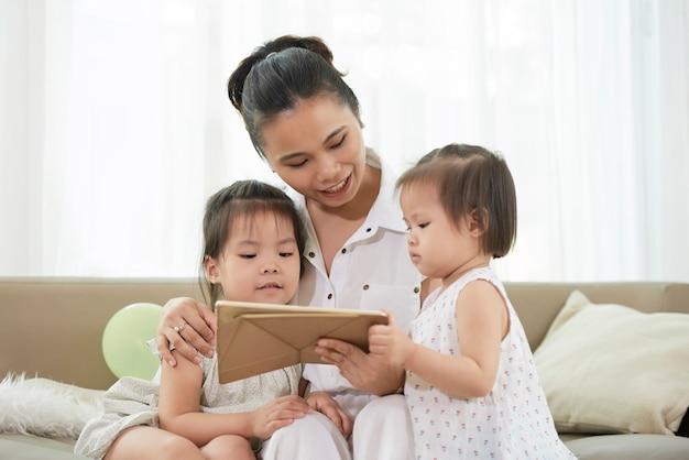 彼女の2人の小さな子供たちに教育アニメを見せて笑顔のかなり若い女性