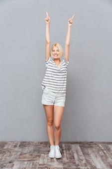 Улыбаясь довольно молодая женщина стоя и указывая обеими руками