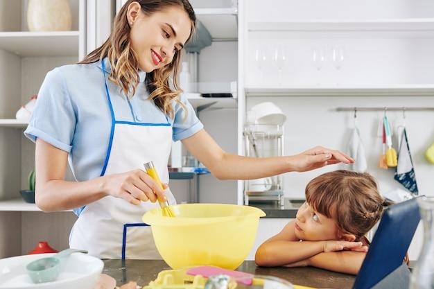 Улыбающаяся симпатичная молодая женщина поглаживает голову дочери, взбивая яйца в большой пластиковой миске