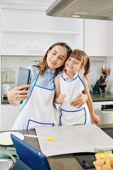 Улыбается симпатичная молодая женщина, делающая селфи с дочерью после совместного выпечки печенья