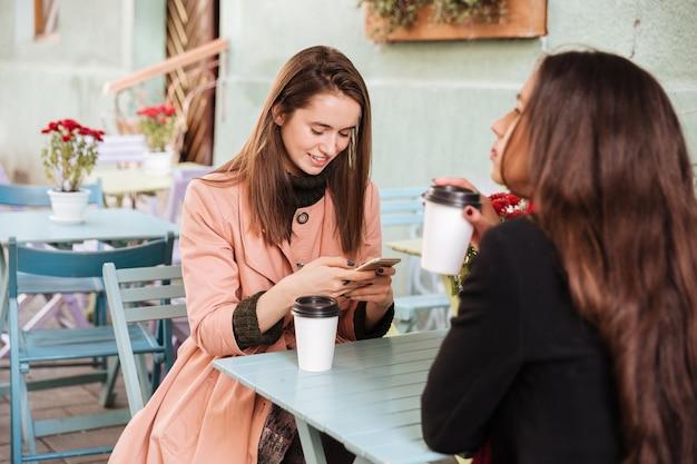 Улыбается симпатичная молодая женщина, использующая свартфон и пьющая кофе со своим другом в летнем кафе