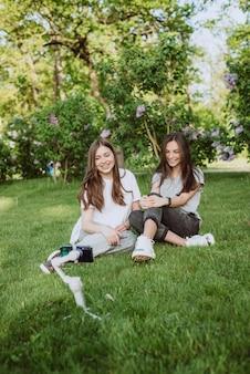 Улыбающиеся симпатичные молодые женщины-блоггеры снимают или записывают видео на свой мобильный телефон на стабилизаторе в солнечном зеленом парке на улице. концепция ведения блога. мягкий выборочный фокус.