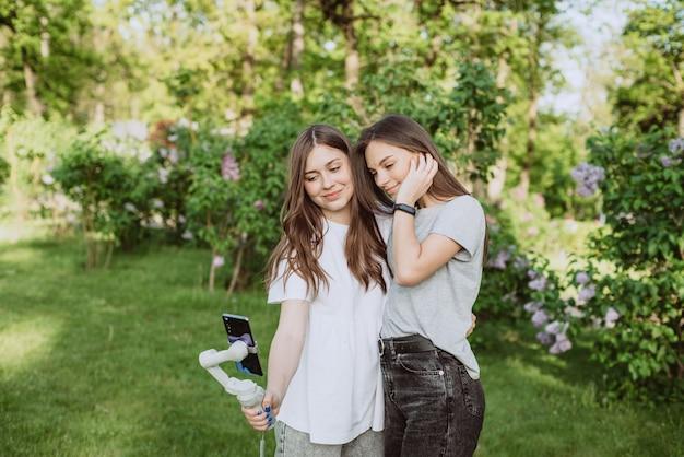 웃고 있는 예쁜 젊은 여성 인플루언서 블로거들이 야외의 햇살 가득한 녹색 공원에서 안정기에 휴대폰으로 비디오를 촬영하거나 녹화하고 있습니다. 블로깅 개념입니다. 부드러운 선택적 초점입니다.