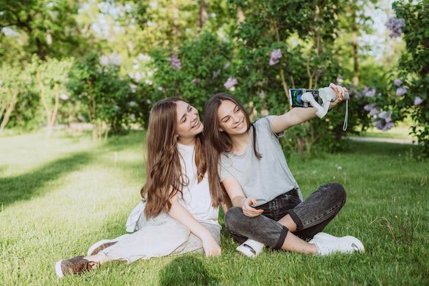 웃고 있는 예쁜 젊은 여성 인플루언서 블로거들이 야외의 햇볕이 잘 드는 녹색 공원에서 스마트폰으로 동영상을 촬영하거나 녹화하고 있습니다. 블로깅 개념입니다. 부드러운 선택적 초점입니다.