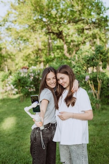 Smiling pretty young women influencer bloggers are filming or recording video with their mobile phone on a stabilizer, in a sunny green park outside. blogging concept. soft selective focus.